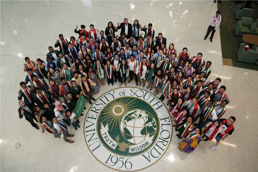 A crowd around the USF seal, looking up to the camera, smiling