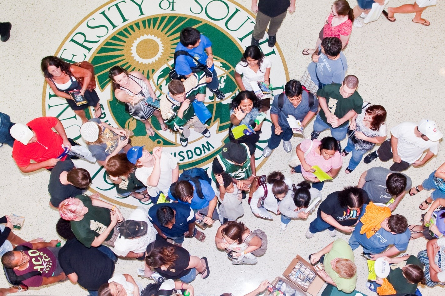 A group of students about the USF seal.