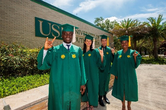 Four graduating students holding up the bulls hand sign