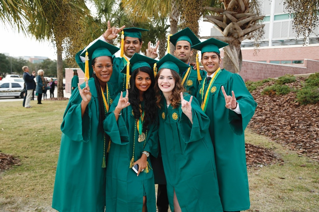 Graduating students holding up the bulls hand sign